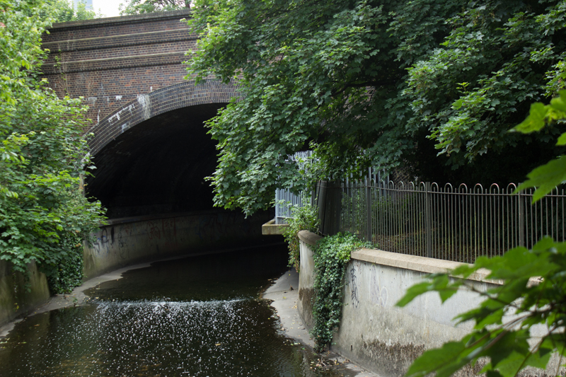 The Ravensbourne disappearing under the railway & behind buildings in River Mill Park