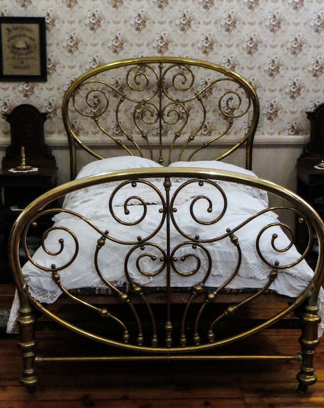 A copper bedstead in a recreated bedroom in the Museum