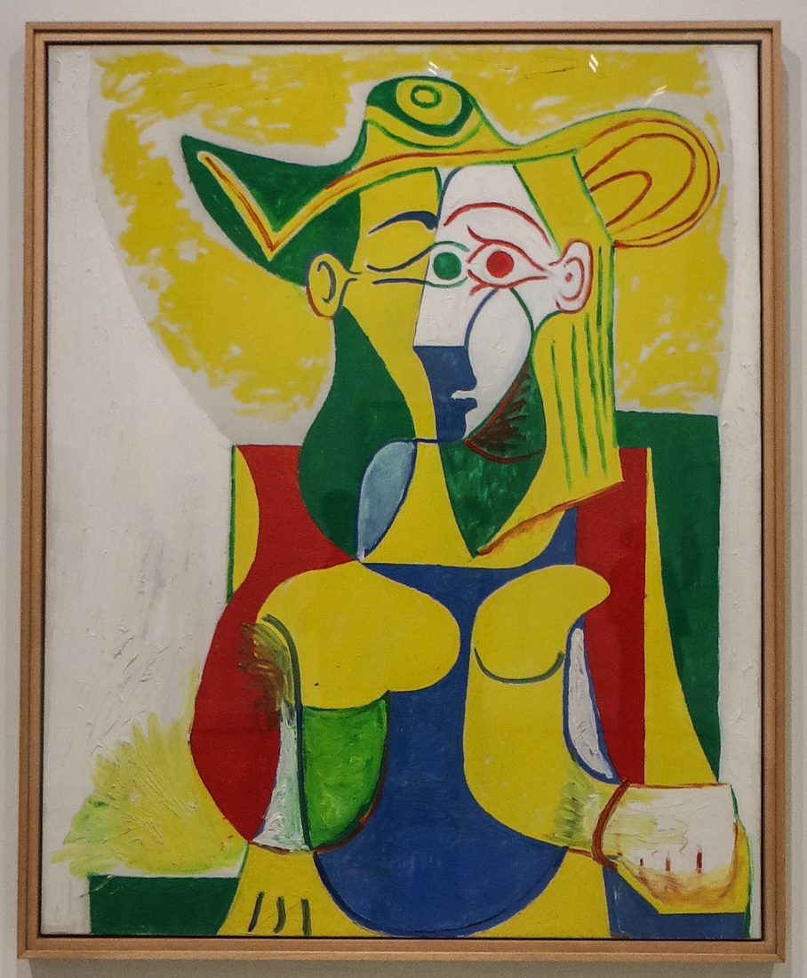 Seated woman in a yellow & green hat, 1962